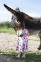 Rear view of girl standing with mule donkey on field - FSIF01474