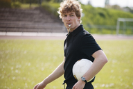 Referee blowing whistle while carrying soccer ball on field - FSIF01495