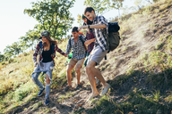 Low angle view of friends climbing mountain in forest - FSIF01498