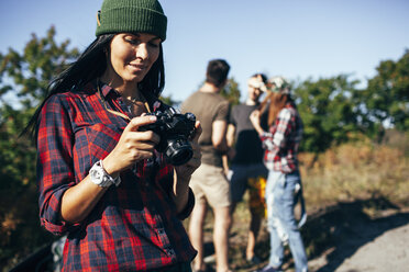 Young woman looking at photographs on camera with friends standing in forest - FSIF01510
