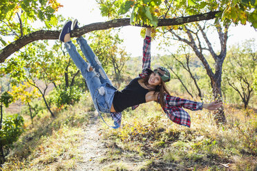 Full length of happy young woman climbing from branch in forest - FSIF01513