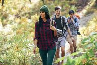 Young woman hiking with friends in forest - FSIF01516