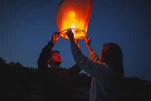 Low angle view of hikers releasing paper lanterns - FSIF01528