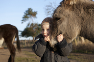 Cute girl embracing donkey on field - FSIF01534