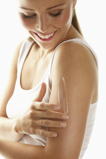 Happy woman applying body lotion on arm against white background - FSIF01546