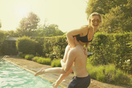 Man throwing cheerful woman in swimming pool during sunny day - FSIF01576