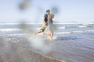 Side view of happy couple running towards sea - FSIF01591