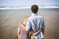 Rear view of loving couple standing arm around at beach - FSIF01597