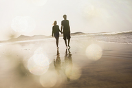 Full length of couple holding hands while walking at beach - FSIF01600