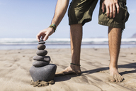 Low section of man balancing stack of stones on beach - FSIF01603