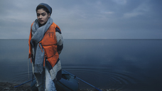 Portrait of teenage girl wearing life jacket while standing at lakeshore - FSIF01615
