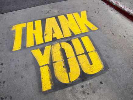 High angle view of yellow thank you text on road - FSIF01636