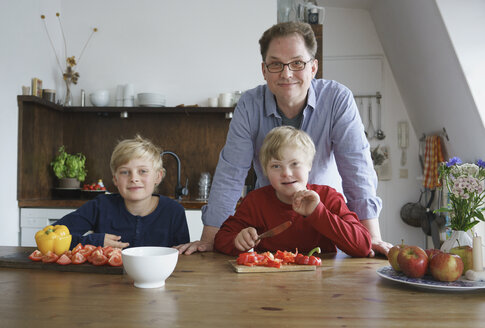 Portrait of father with sons sitting at table in kitchen - FSIF01648