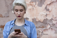 Beautiful woman using phone while standing against old wall - FSIF01672