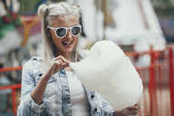 Fashionable young woman wearing sunglasses while eating cotton candy outdoors - FSIF01681