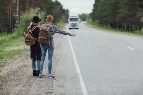 Rear view of couple hitchhiking on roadside against trees - FSIF01693