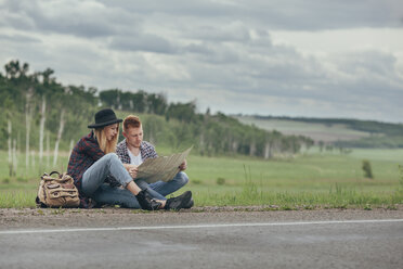 Couple reading map while sitting on roadside against sky - FSIF01699