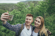 Smiling couple taking selfie through smart phone at forest - FSIF01702