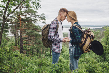 Loving couple holding hands while standing amidst plants at forest - FSIF01705
