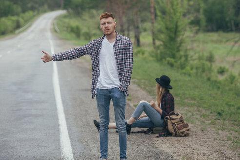 Man hitchhiking while woman sitting on roadside - FSIF01708