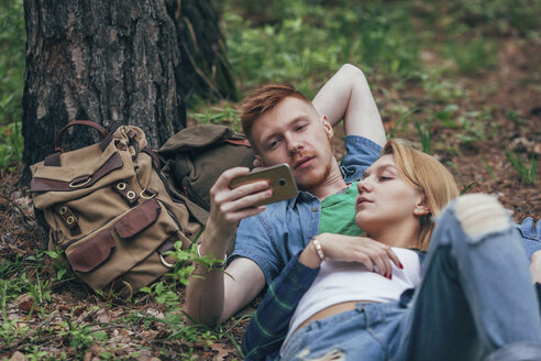 Young couple looking in smart phone while lying by tree at forest - FSIF01714