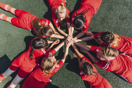 High angle view of sports team stacking hands on field - FSIF01744