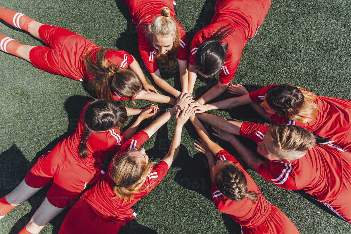 High angle view of sports team stacking hands on field - FSIF01744 - fStop/Westend61