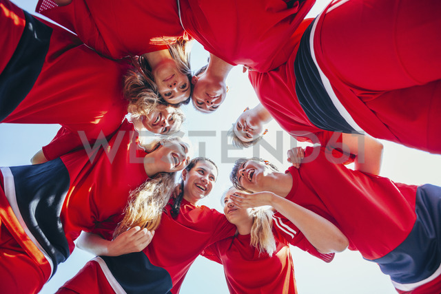 Cheerful soccer players talking while huddling against clear sky - FSIF01753