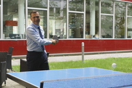 Confident happy businessman playing table tennis at creative office - FSIF01780
