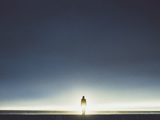 Silhouette man standing on seashore against clear sky during sunny day - FSIF01810