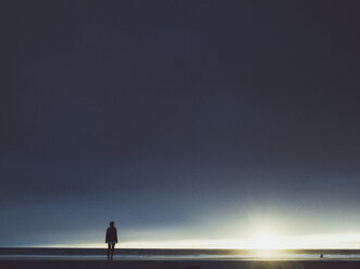 Woman standing on seashore against cloudy sky during sunny day - FSIF01813