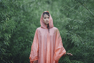 Young woman wearing raincoat standing amidst plants during rainy season - FSIF01816
