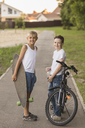 Smiling friends with skateboard and bicycle standing at park - FSIF01825