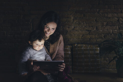 Mother and daughter using digital tablet at home in the dark - GEMF01884