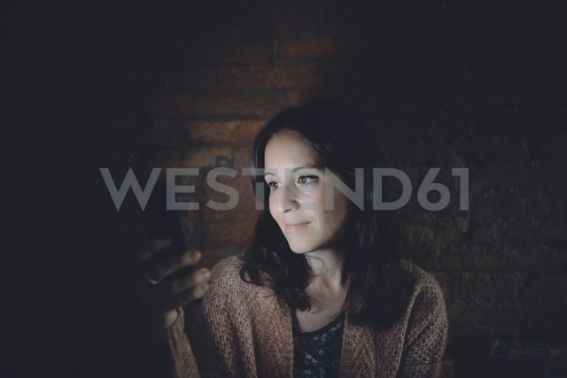 Portrait of woman using smartphone at home in the dark - GEMF01887