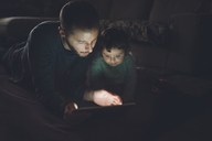 Father and daughter looking at   digital tablet at home in the dark - GEMF01890
