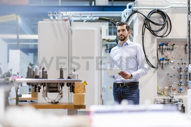 Businessman in factory holding tablet - DIGF03386