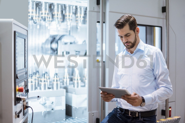 Businessman at machine in factory looking at tablet - DIGF03395