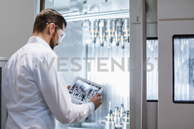 Man wearing lab coat and safety goggles at machine in factory looking at tablet - DIGF03398 - Daniel Ingold/Westend61