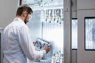 Man wearing lab coat and safety goggles at machine in factory looking at tablet - DIGF03398