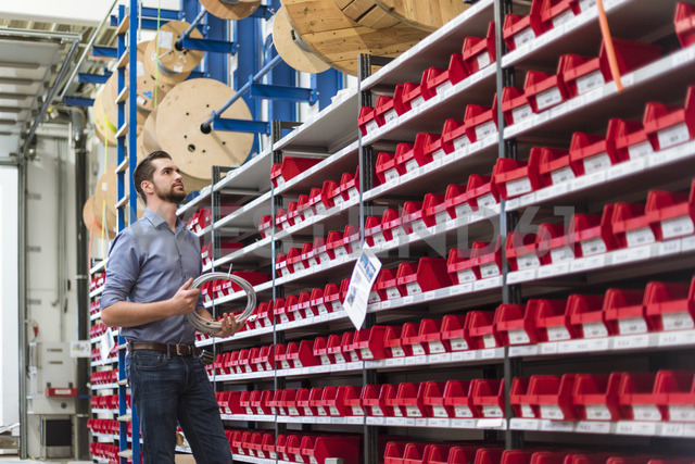 Man standing at shelf in storehouse holding cable - DIGF03401