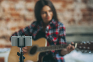 Smart phone in monopod with woman playing guitar in background at home - FSIF01843