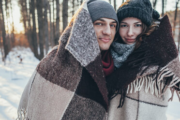 Portrait of smiling couple wrapped in blanket while standing on snow covered field - FSIF01849