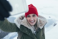 Smiling young woman taking selfie on smart phone during winter - FSIF01852