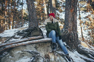 Full length of young woman sitting in snow covered forest - FSIF01855
