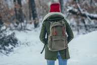 Rear view of young woman with backpack standing on snow covered field - FSIF01858
