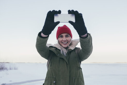 Young woman taking selfie on smart phone during winter - FSIF01861