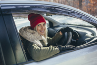Portrait of happy beautiful woman driving car during winter - FSIF01867