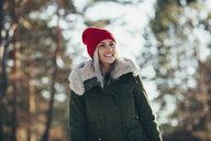 Low angle view of happy young woman wearing knit hat and jacket while looking away - FSIF01870