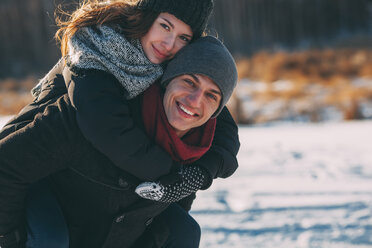 Portrait of happy man giving piggyback ride to woman during winter - FSIF01873